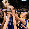 Broomfield High School player senior Bre Burgesser, center, joins the rest of her team to touch the championship trophy during the Colorado High School Athletic Association girls class 4A championship game on Friday, March 11, at the Coors Events Center on the University of Colorado campus in Boulder. Broomfield defeated Longmont 48-38.<br /> Jeremy Papasso/ Camera