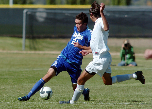 Cole Chapleski, left, Broomfield, kicks the ball past Chris Gurule,  Niwot, during Saturday's game at Niwot High.<br /> <br /> October 3, 2009<br /> Staff photo/David R. Jennings