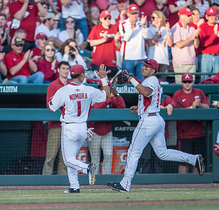 Arkansas infielder Rick Nomura (1) and Arkansas infielder Michael Bernal (3) celebrate the end of an inning during a baseball game between Arkansas and Central Michigan on 2-19-16.   (Alan Jamison, Nate Allen Sports Service)