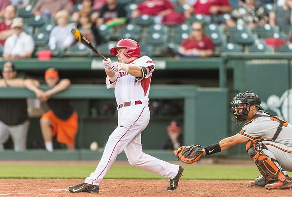 Arkansas infielder Cody Scroggins (5) bats during a baseball game between Arkansas and Oklahoma State University on 4/26/2016.   (Alan Jamison, Nate Allen Sports Service)