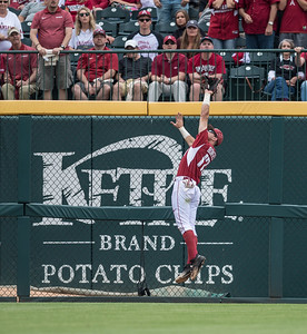 Arkansas outfielder Luke Bonfield (17) jumps high to prevent a home run during a baseball game between Arkansas and Texas A&M University on 4/30/2016.   (Alan Jamison, Nate Allen Sports Service)