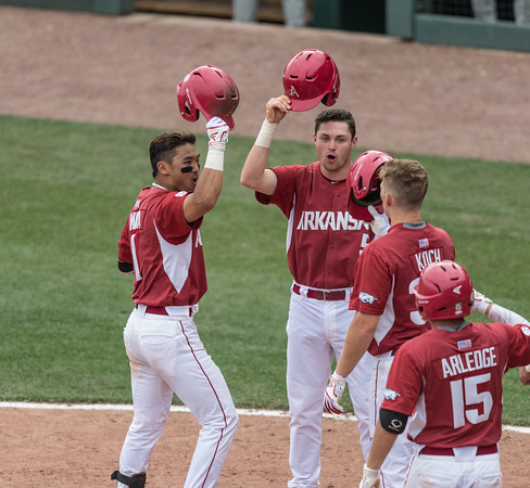 Arkansas Razorbacks infielder Rick Nomura (1) and Cody Scroggins (5) celebrate Nomura's home run with teammates during a baseball game between Alabama and Arkansas on May 15,  2016.  (Alan Jamison, Nate Allen Sports Service)