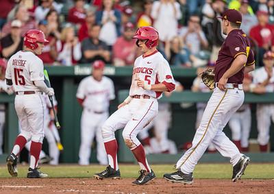 Arkansas infielder Cody Scroggins (5) scores during a baseball game between Arkansas and Central Michigan on 2-19-16.   (Alan Jamison, Nate Allen Sports Service)