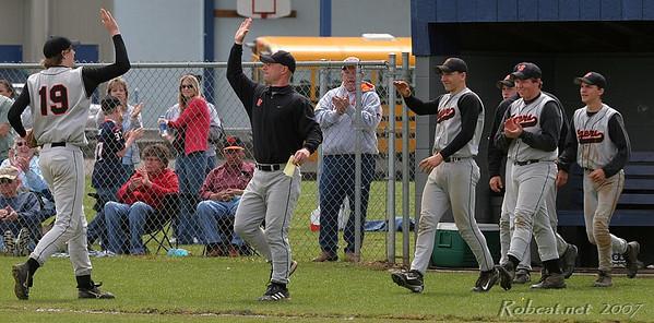 Napavine's Kellen Ashmore (#19 pitcher) celebrates win with coach Josh Fay and team.