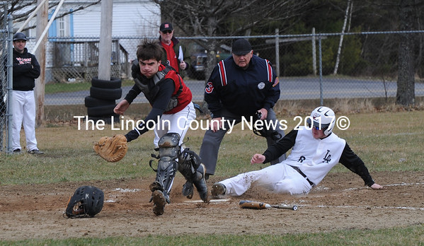 Chris Gove scores for Lincoln Academy as Wolverine catcher Cody Graves chases down a wild throw.