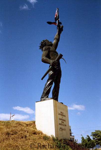 Statue dedicated to the Revolution, outside Managua. The typical machine gun in left hand is balanced by the pick in his right.