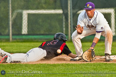 Reynoldsburg High School's #15 Jeff Murray makes the catch as St. Charles High School's #5 Michael Mackessy safely touches back to first base at Reynoldsburg Junior High School Thursday evening May 13, 2010. (©James D. DeCamp | http://www.JamesDeCamp.com | 614-367-6366)