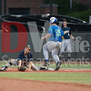 Erik Brodkowitz (13) scores a run as the Catonsville catcher stretches his body to it's limits to prevent the score.