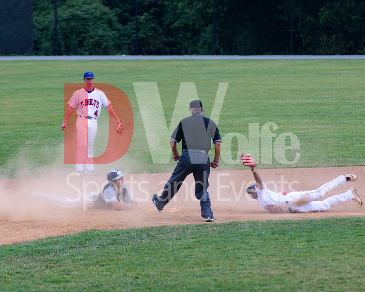T-Bolts infielder Grayland Fowler holds the ball in his glove high for the referee to see,  as Gaithersburg Giants player Tate Shaw looks up from the dust cloud  hoping for a favorable call.  Shaw was called out.