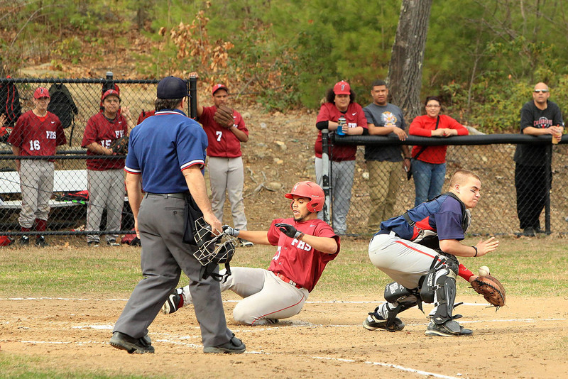 Fitchburg's Joel Luna is safe at home plate as the throw comes in to North Middlesex catcher Jared Borneman. SENTINEL & ENTERPRISE / SCOTT LAPRADE