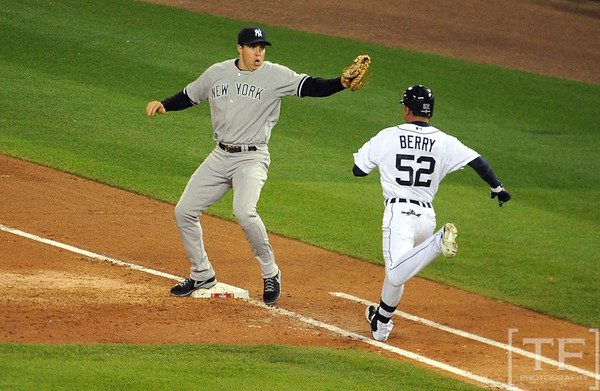 Oct 16, 2012; Detroit, MI, USA; Detroit Tigers left fielder Quintin Berry (52) is forced out by New York Yankees first baseman Mark Teixeira (left) in the 3rd inning during game three of the 2012 ALCS at Comerica Park.  Mandatory Credit: Tim Fuller-USA TODAY Sports