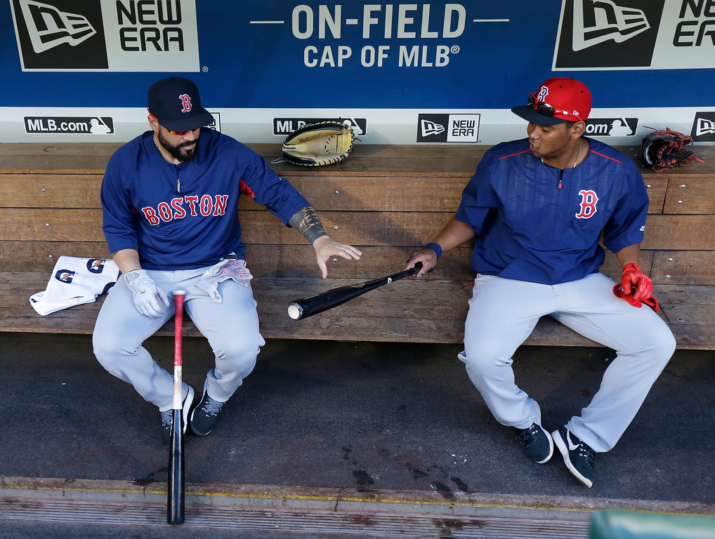 . Boston Red Sox third baseman Rafael Devers, right, shows his bat to catcher Sandy Leon, left, as they sit in the dugout before batting practice prior to a baseball game against the Seattle Mariners, Monday, July 24, 2017, in Seattle. (AP Photo/Ted S. Warren)