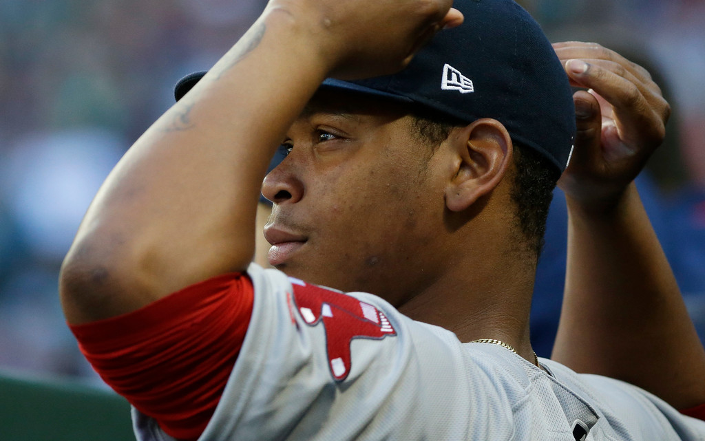 . Boston Red Sox third baseman Rafael Devers adjusts his cap as he sits in the dugout during the second inning of a baseball game against the Seattle Mariners, Monday, July 24, 2017, in Seattle. (AP Photo/Ted S. Warren)