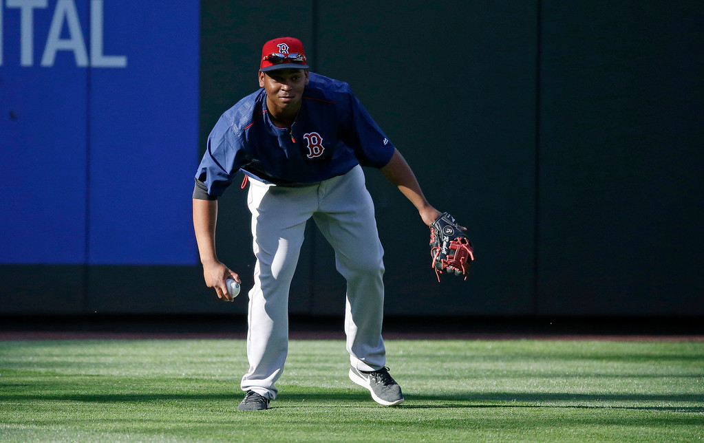 . Boston Red Sox third baseman Rafael Devers fields a ball in the outfield during batting practice before a baseball game against the Seattle Mariners, Monday, July 24, 2017, in Seattle. (AP Photo/Ted S. Warren)
