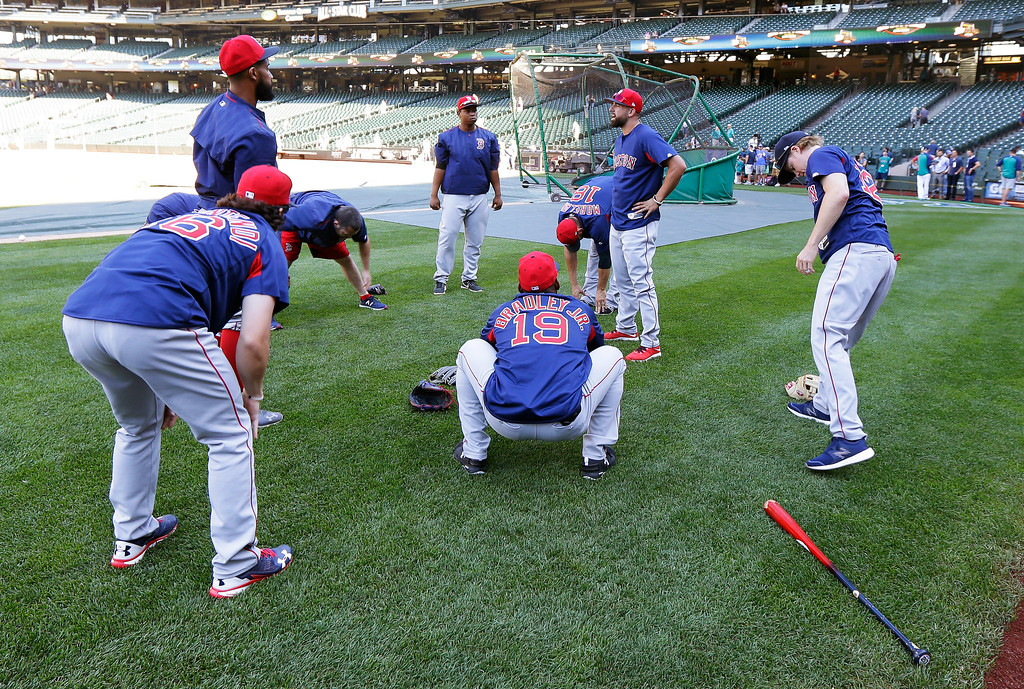 . Boston Red Sox third baseman Rafael Devers, center rear, stretches with teammates before batting practice prior to a baseball game against the Seattle Mariners, Monday, July 24, 2017, in Seattle. (AP Photo/Ted S. Warren)