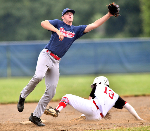 WARREN  DILLAWAY   Star Beacon <br /> Gordon Seger, of the Bruisers, leaps for the ball as Anthony Arkey slides safely into third base for the Elite on Friday evening during American Legion action at Grand River Academy.