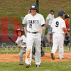 Colin Shaw (17) walks to the dugout after scoring a run while the unidentified bat boy collects the bat from the ground.