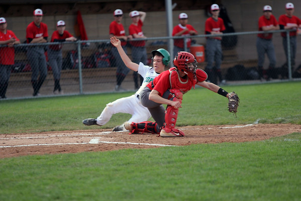 GREG KEIM | THE GOSHEN NEWS<br /> Junior Quinn Miller of the Concord Minutemen slides safely into home around Goshen's sophomore catcher Philip Wertz in a high school baseball game Friday night at Concord.