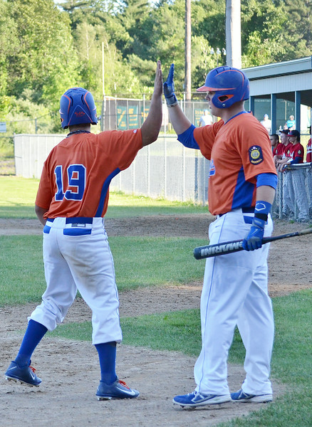 Leominster American Legion's Brett Corliss high fives Marc Poirier after scoring a run on Thursday evening against Grafton Hill, who came away with the 13-4 win. SENTINEL & ENTERPRISE / Ashley Green
