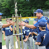 American League president, Rob Lora, hands over the trophy to Leominster National's coach, Steve Richard after National's championship victory on Sunday at Desantis Field.
