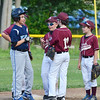 Opponents make nice during a pitching change in the Leominster Little League City Championship at Justin DeSantis Field on Wednesday night. SENTINEL & ENTERPRISE / Ashley Green