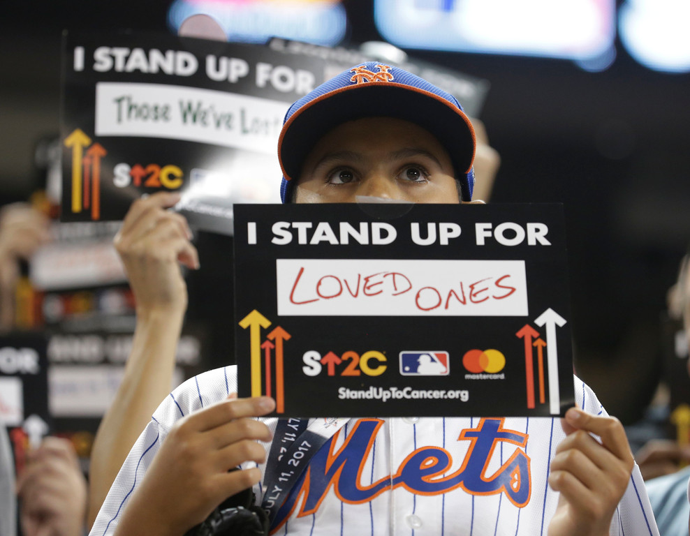. A baseball fan remembers a loved one during moment to remember those that have been affected by cancer, during the MLB baseball All-Star Game, Tuesday, July 11, 2017, in Miami. (AP Photo/Lynne Sladky)