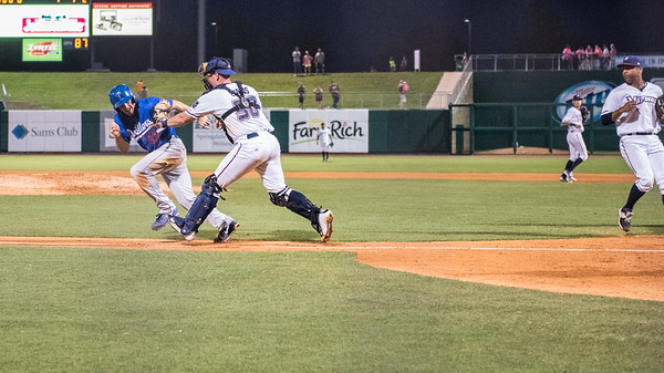 Northwest Arkansas Naturals catcher Zane Evans (30) tags out Tulsa Drillers third baseman Jarek Cunningham (37) during the NWA Naturals vs Tulsa Drillers ballgame at Arvest Ballpark in Springdale, Arkansas, on Thursday, June 25, 2015.  The Drillers won 3-2.  Photos by Alan Jamison.