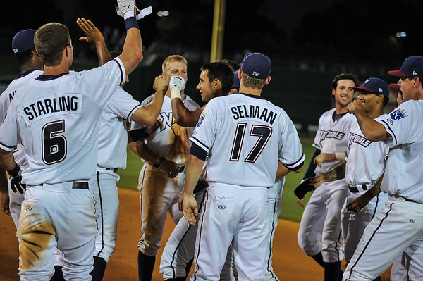 Celebration for a Northwest Arkansas Naturals right fielder Lane Adams (19) walk-off single in a ballgame between the NWA Naturals and the Tulsa Drillers at Arvest Ballpark in Springdale, Arkansas, on Saturday, June 27, 2015.  The Naturals won 2-1 in extra innings.  Photos by Alan Jamison.