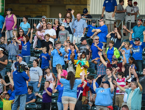 Fans stretch during the seventh inning of a ballgame between the NWA Naturals and the Tulsa Drillers at Arvest Ballpark in Springdale, Arkansas, on Saturday, June 27, 2015.  The Naturals won 2-1 in extra innings.  Photos by Alan Jamison.