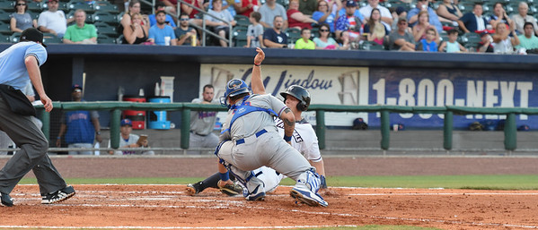 Northwest Arkansas Naturals third baseman Hunter Dozier (9) slides into home plate and was tagged out by Midland catcher Bruce Maxwell (13) in a baseball game between the NWA Naturals and the Midland RockHounds at Arvest Ballpark in Springdale, Arkansas, on Sunday, July 12, 2015.  The RockHounds won 2-0.  Photos by Alan Jamison.