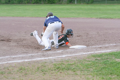 Austin Hillis returns to first base during a pick off in their game against Alliance on Monday.