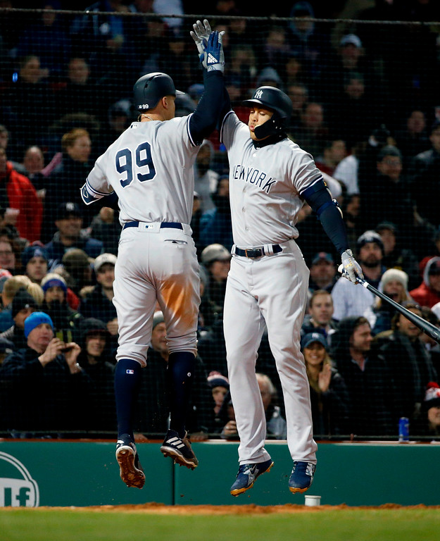 . New York Yankees\' Aaron Judge (99) celebrates his solo home run with Giancarlo Stanton during the fifth inning of a baseball game against the Boston Red Sox in Boston, Tuesday, April 10, 2018. (AP Photo/Michael Dwyer)