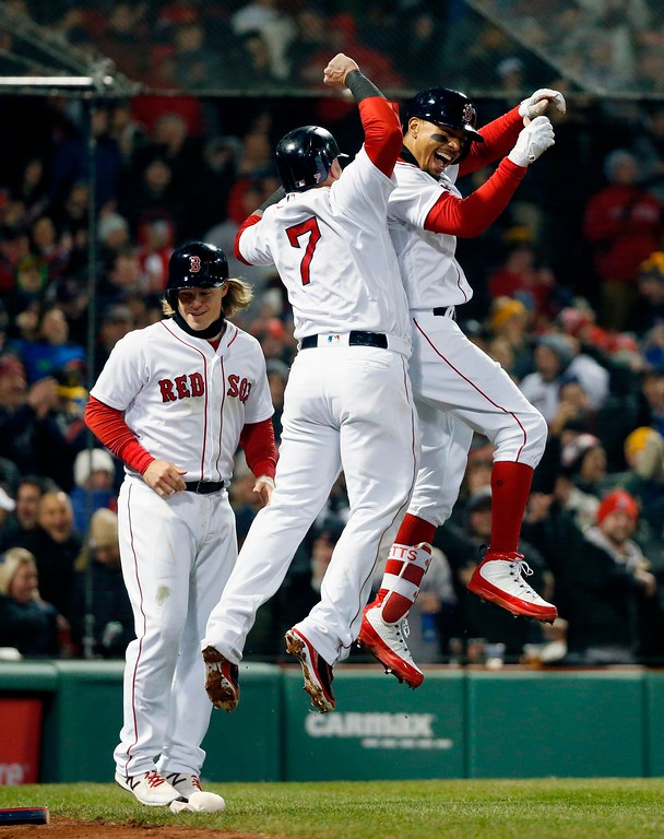 . Boston Red Sox\'s Mookie Betts, right, celebrates with Christian Vazquez (7) and Brock Holt, left, after Betts\' grand slam during the sixth inning of a baseball game against the New York Yankees in Boston, Tuesday, April 10, 2018. (AP Photo/Michael Dwyer)