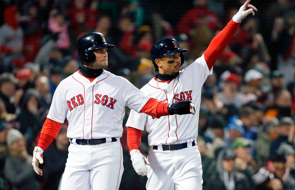 . Boston Red Sox\'s Mookie Betts, right, and Andrew Benintendi signal to Boston Red Sox\'s J.D. Martinez after scoring on Martinez\'s two-run double during the sixth inning of a baseball game against the New York Yankees in Boston, Tuesday, April 10, 2018. (AP Photo/Michael Dwyer)