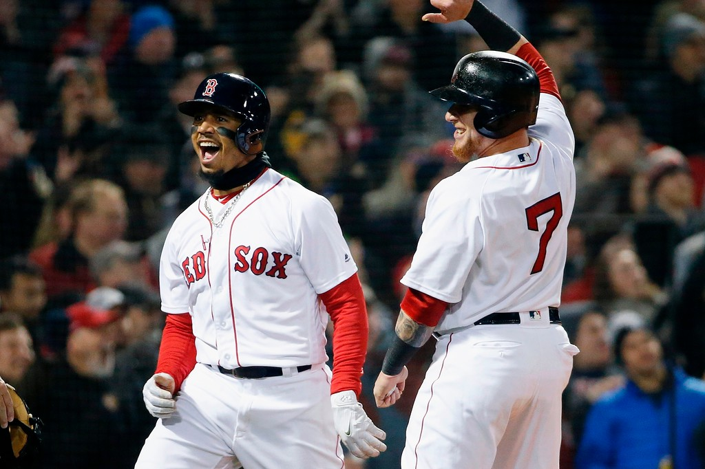 . Boston Red Sox\'s Mookie Betts, left, celebrates with Christian Vazquez (7) after scoring on a triple by Andrew Benintendi during the second inning of a baseball game against the New York Yankees in Boston, Tuesday, April 10, 2018. (AP Photo/Michael Dwyer)