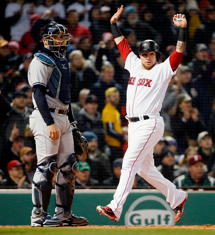 . Boston Red Sox\'s Christian Vazquez, right, celebrates in front of New York Yankees\' Austin Romine after scoring on a triple by Andrew Benintendi during the second inning of a baseball game in Boston, Tuesday, April 10, 2018. (AP Photo/Michael Dwyer)