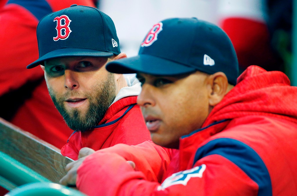 . Boston Red Sox\'s Dustin Pedroia, left, sits in the dugout with manager Alex Cora before a baseball game against the New York Yankees in Boston, Tuesday, April 10, 2018. (AP Photo/Michael Dwyer)