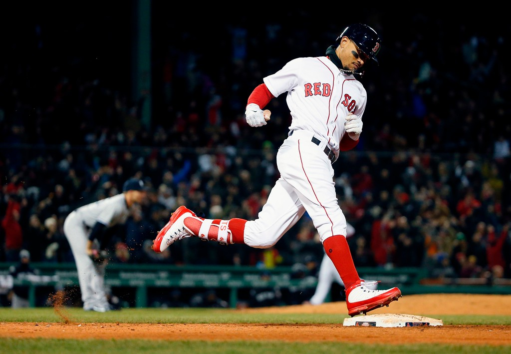 . Boston Red Sox\'s Mookie Betts rounds first base on his grand slam off New York Yankees\' Chasen Shreve, left, during the sixth inning of a baseball game in Boston, Tuesday, April 10, 2018. (AP Photo/Michael Dwyer)