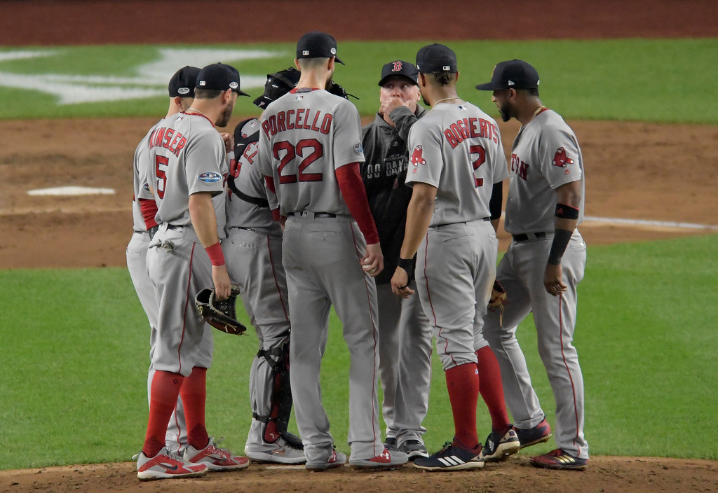 . Boston Red Sox pitching coach Dana LeVangie, center, talks with starting pitcher Rick Porcello (22) on the mound during the fifth inning of Game 4 of baseball\'s American League Division Series against the New York Yankees, Tuesday, Oct. 9, 2018, in New York. (AP Photo/Bill Kostroun)