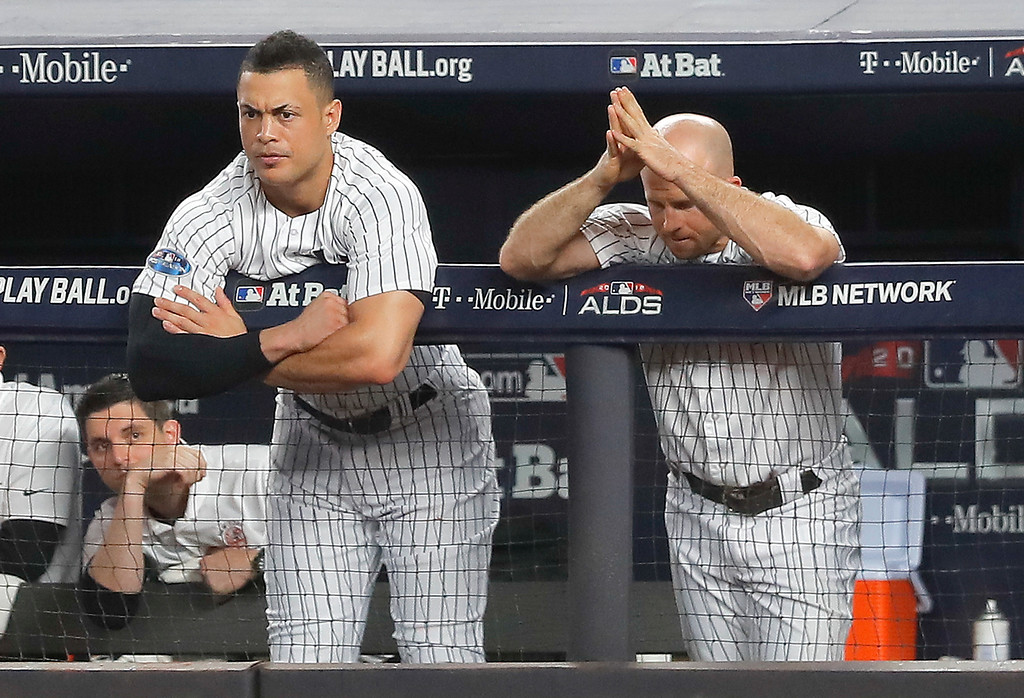 . New York Yankees\' Giancarlo Stanton, left, and Brett Gardner watch play from the dugout during the seventh inning of Game 4 of baseball\'s American League Division Series against the Boston Red Sox, Tuesday, Oct. 9, 2018, in New York. (AP Photo/Julie Jacobson)