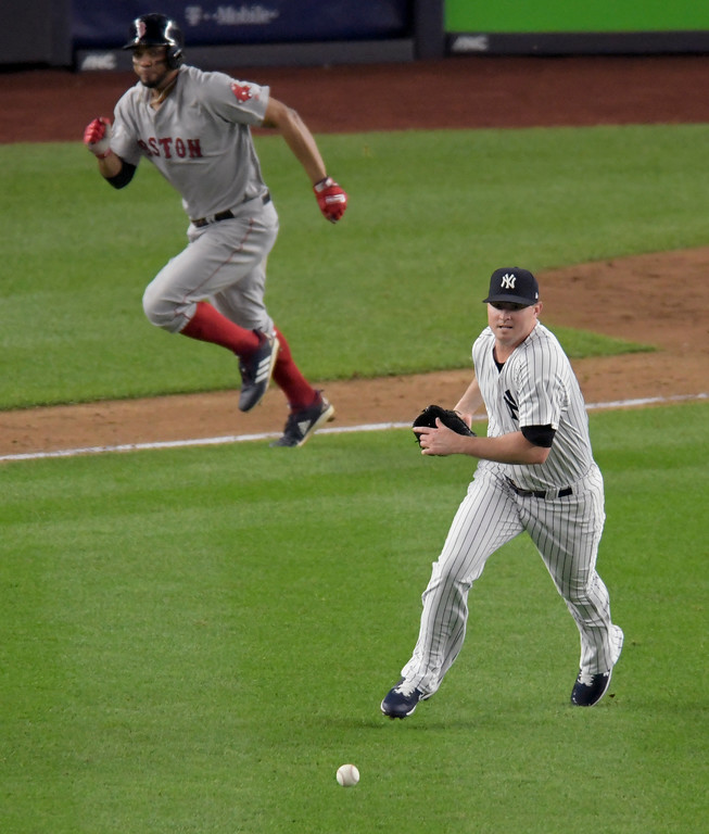 . New York Yankees relief pitcher Zach Britton chases down a ground ball he deflected hit by Boston Red Sox\'s Xander Bogaerts during the fifth inning of Game 4 of baseball\'s American League Division Series, Tuesday, Oct. 9, 2018, in New York. (AP Photo/Bill Kostroun)