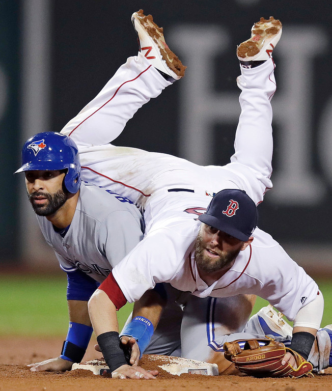 . Boston Red Sox second baseman Dustin Pedroia lands on Toronto Blue Jays\' Jose Bautista after turning a double play during the 11th inning of a baseball game at Fenway Park in Boston, Tuesday, July 18, 2017. Russell Martin was out at first. (AP Photo/Charles Krupa)