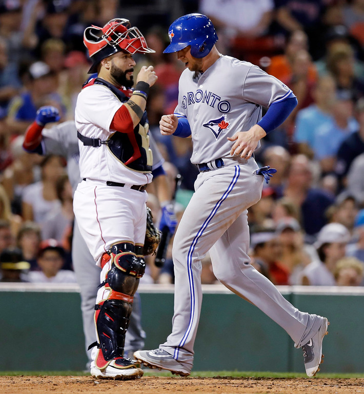 . Toronto Blue Jays\'s Justin Smoak, right , crosses home plate to score on a single by Troy Tulowitzki during the fifth inning of a baseball game at Fenway Park in Boston, Tuesday, July 18, 2017. At left is Boston Red Sox catcher Sandy Leon. (AP Photo/Charles Krupa)