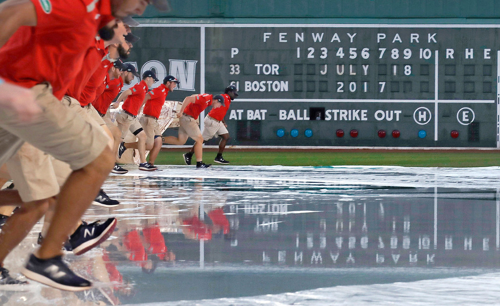 . The grounds crew removes the tarp, completely filled with rain water, after a heavy storm passed over prior to a baseball game between the Boston Red Sox and Toronto Blue Jays at Fenway Park in Boston, Tuesday, July 18, 2017. The start of the game was delayed for about an hour. (AP Photo/Charles Krupa)