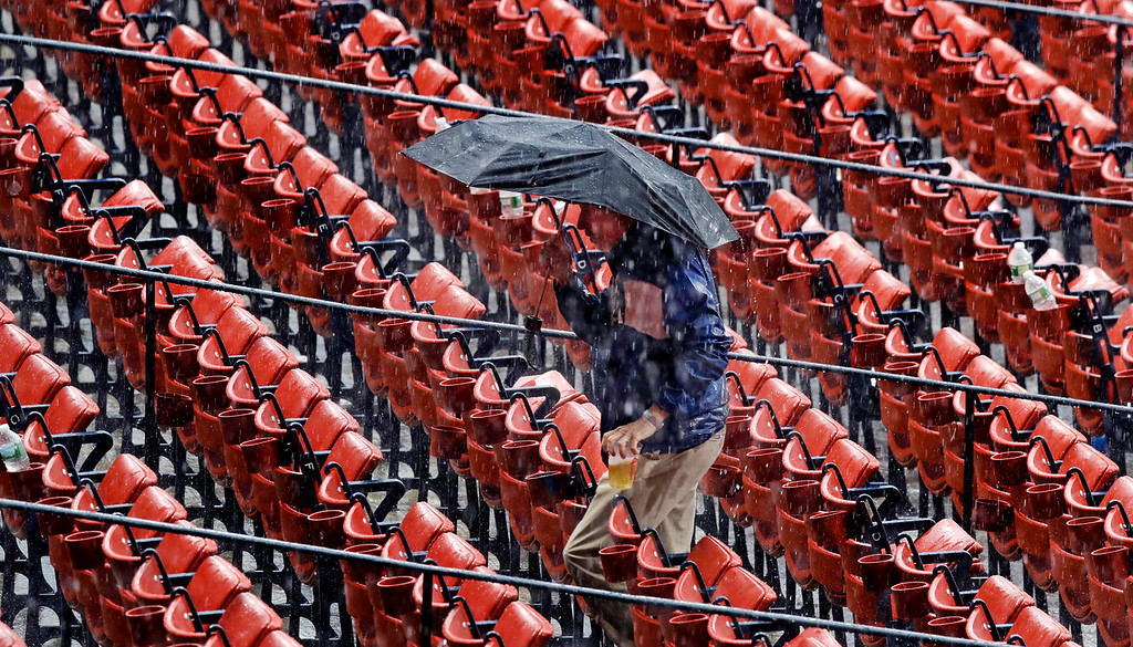 . A fan retrieves his beer, after leaving at his seat\'s cup holder, during a heavy rain storm prior to a baseball game between the Boston Red Sox and Toronto Blue Jays at Fenway Park in Boston, Tuesday, July 18, 2017. The start of the game was delayed for about an hour. (AP Photo/Charles Krupa)