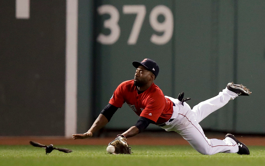 . Boston Red Sox center fielder Jackie Bradley Jr. dives for a single by New York Yankees\' Aaron Judge during the seventh inning of Game 1 of a baseball American League Division Series on Friday, Oct. 5, 2018, in Boston. (AP Photo/Charles Krupa)
