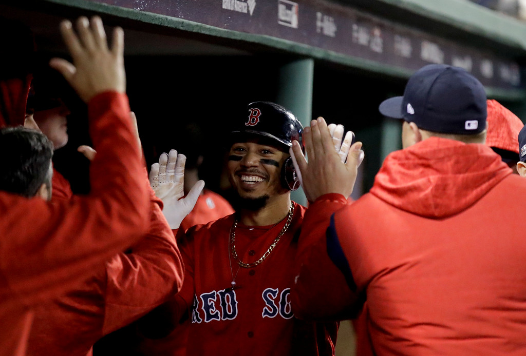 . Boston Red Sox\'s Mookie Betts celebrates in the dugout after scoring of a single by Steve Pearce during the third inning of Game 1 of a baseball American League Division Series against the New York Yankees on Friday, Oct. 5, 2018, in Boston. (AP Photo/Charles Krupa)