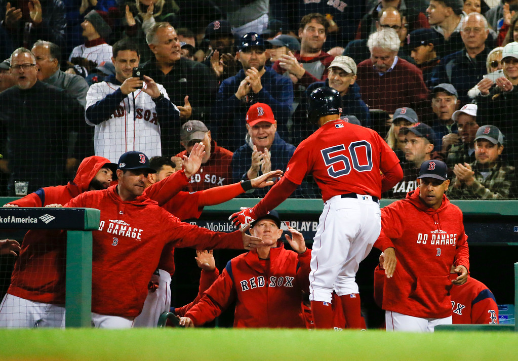 . Boston Red Sox\'s Mookie Betts celebrates in the dugout after scoring of a single by Steve Pearce during the third inning of Game 1 of a baseball American League Division Series against the New York Yankees on Friday, Oct. 5, 2018, in Boston. (AP Photo/Elise Amendola)