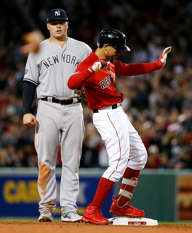 . Boston Red Sox\'s Mookie Betts, right, celebrates after a double against the New York Yankees during the third inning of Game 1 of a baseball American League Division Series on Friday, Oct. 5, 2018, in Boston. (AP Photo/Elise Amendola)
