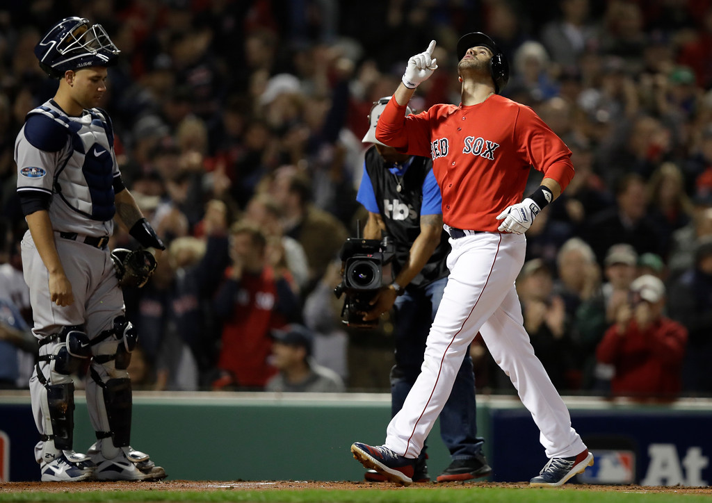 . Boston Red Sox\'s J.D. Martinez points skyward after his three-run home run, next to New York Yankees catcher Gary Sanchez during the first inning of Game 1 of a baseball American League Division Series against the New York Yankees on Friday, Oct. 5, 2018, in Boston. (AP Photo/Charles Krupa)